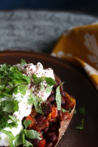 Smokey chipotle black bean filled sweet potatoes topped with a creamy feta sauce brings warmth and comfort when it's cold and rainy outside.