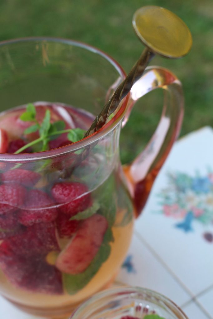 Late Summer Punch Cocktail with rum, sparkling wine, peaches and raspberries. Perfect for parties.